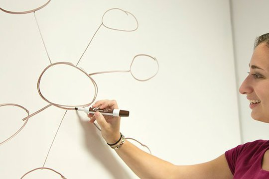 Woman drawing a sketch in a whiteboard