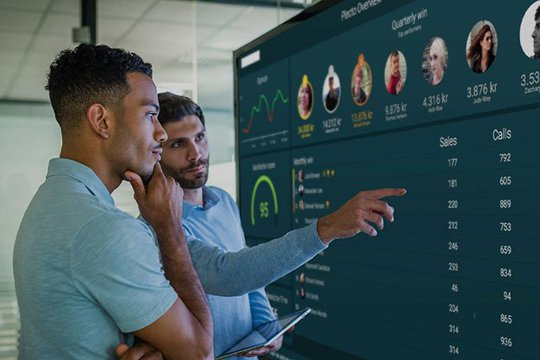 Two employees looking at a Plecto dashboard in the office